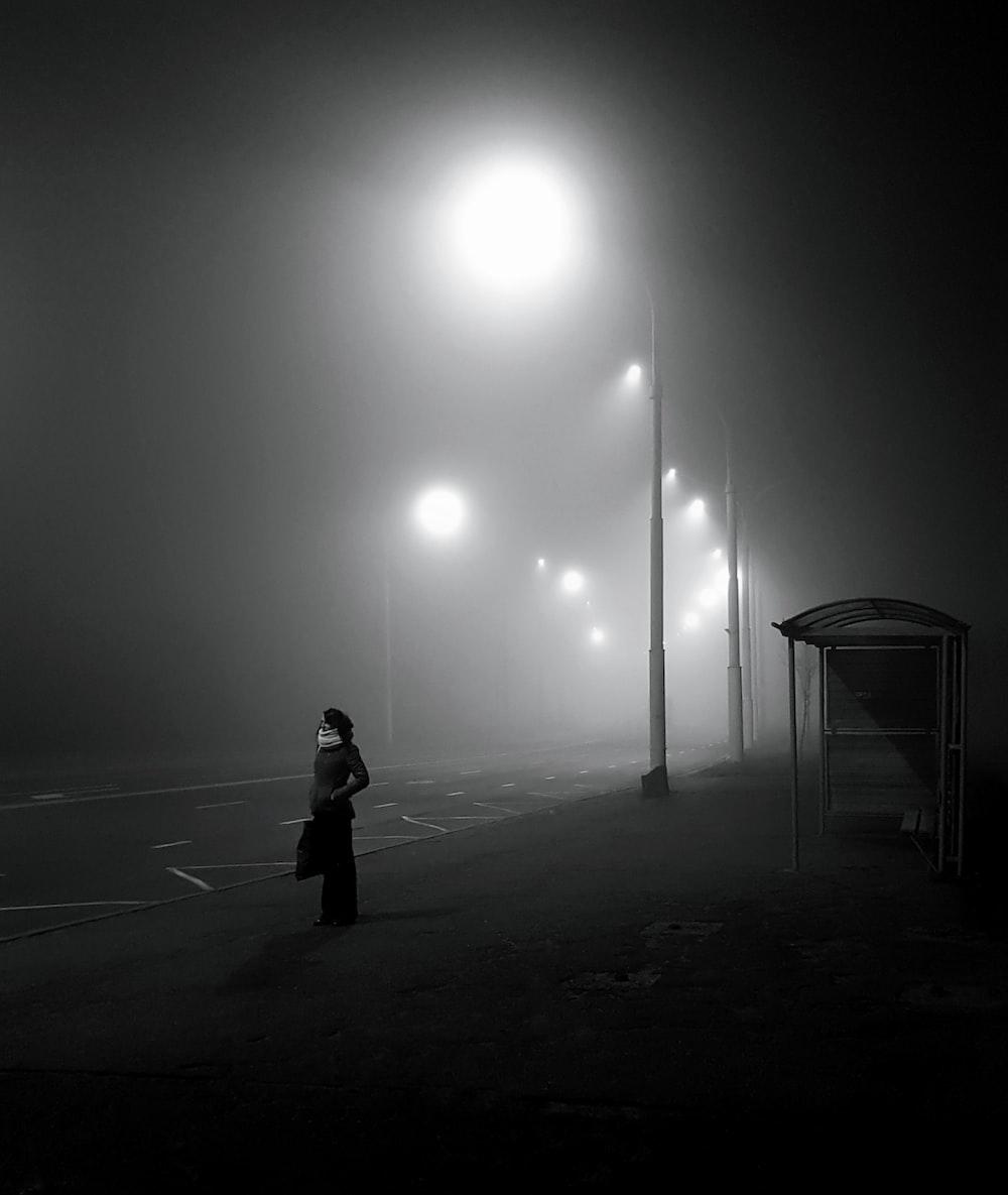 woman standing near light lamppost