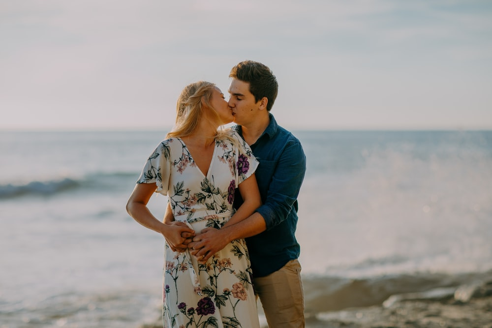 selective focus photography of couple on shoreline