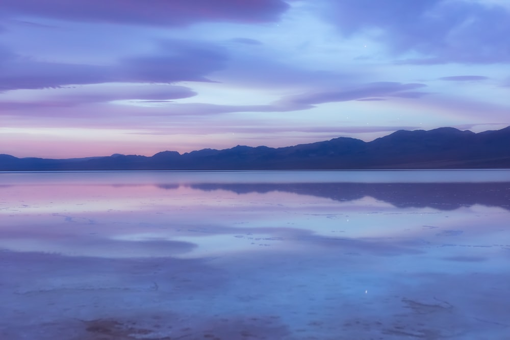 landscape photo of mountains near body of water under cloudsky