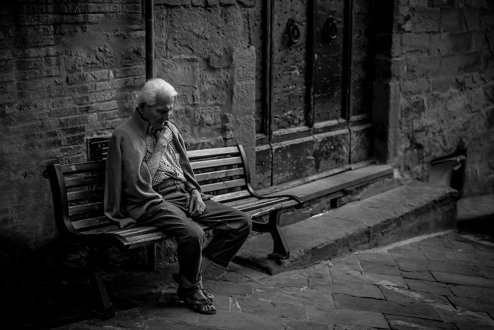 man sitting on brown bench