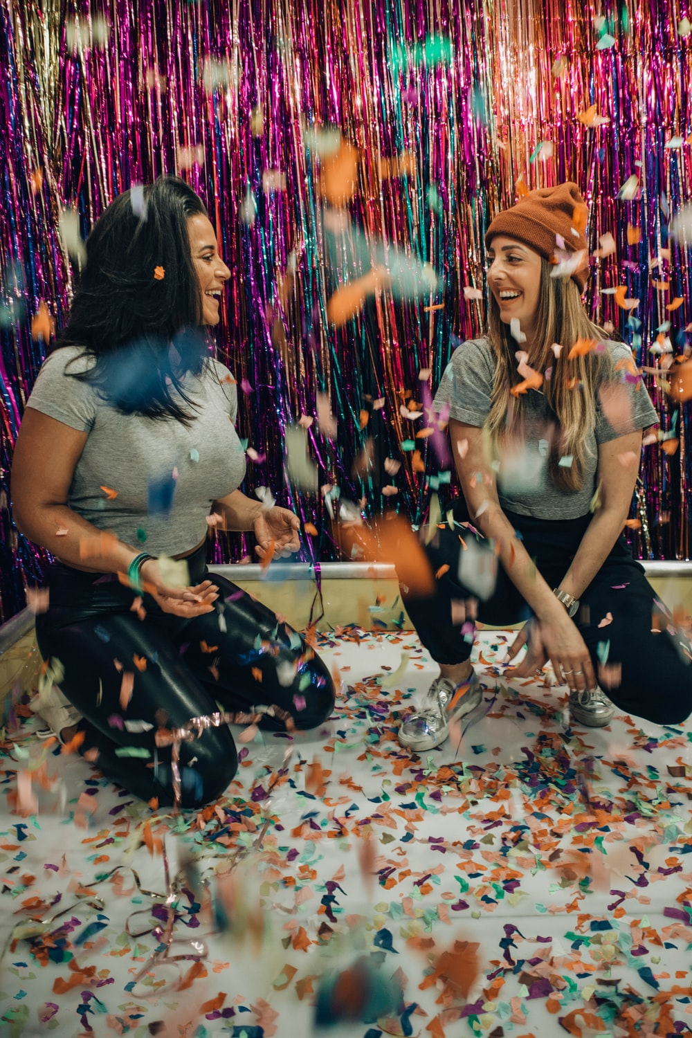 two women kneeling under falling confetti