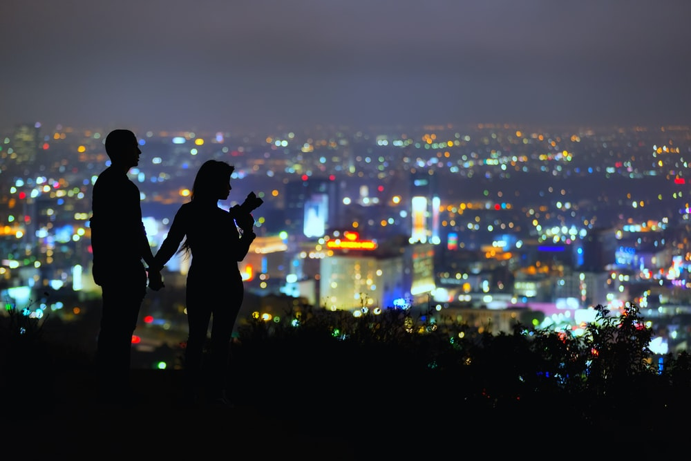 couple standing on hill overlooking city at night