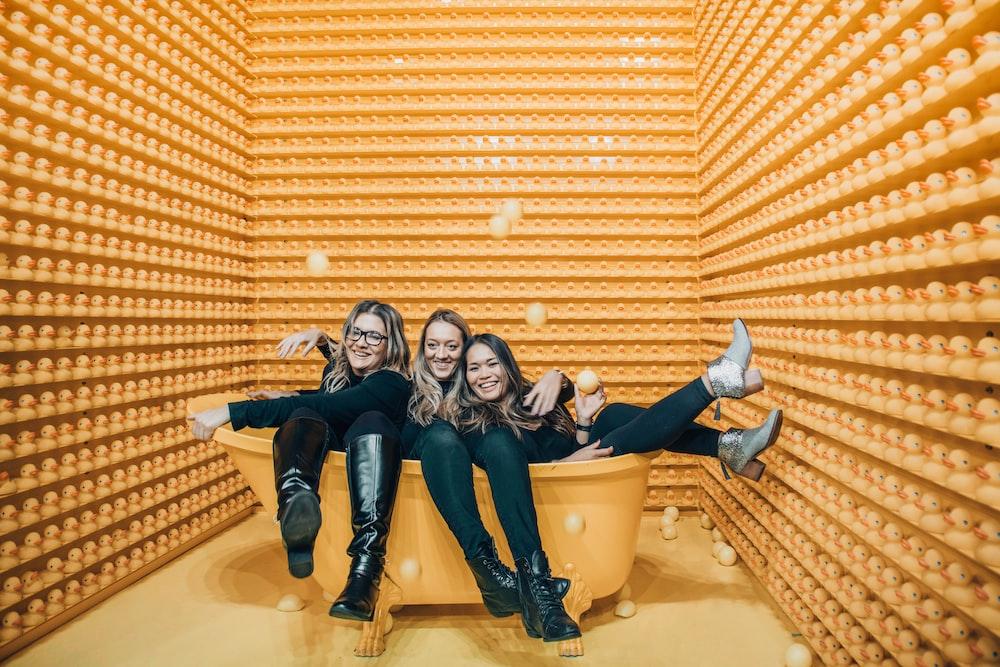 three women sitting inside bathtub