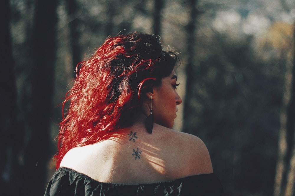 woman showing her back tattoo outdoors