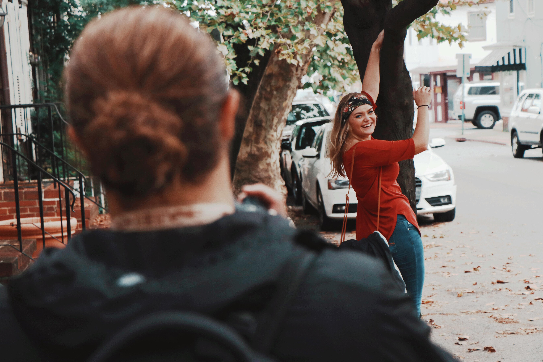 woman standing beside tree near road