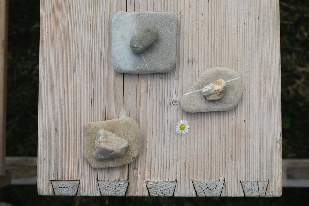 three gray stones on beige board panel