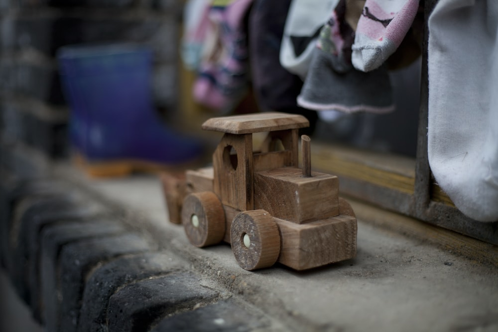 brown wooden vehicle toy on gray concrete surface