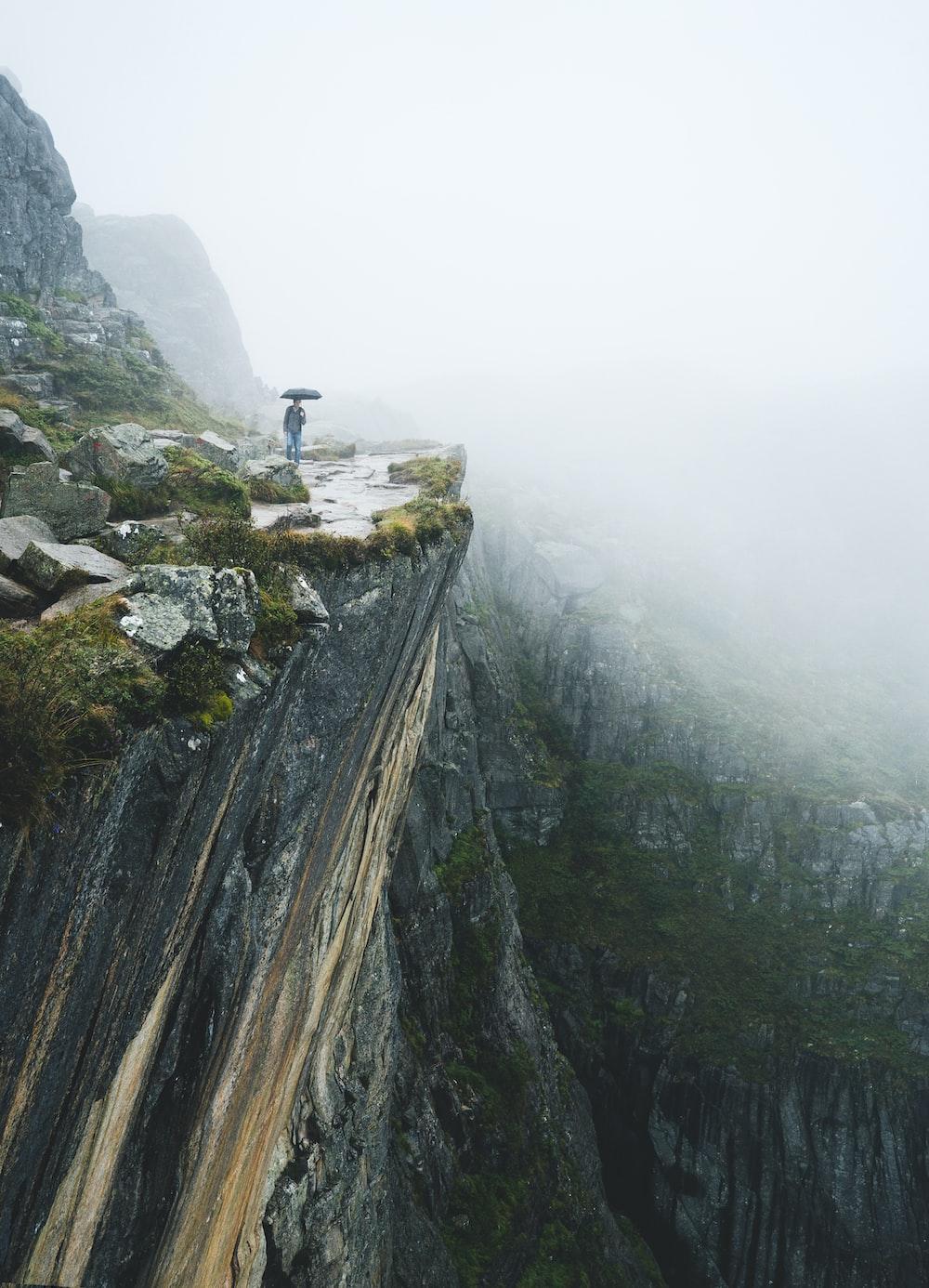 person walking near cliff