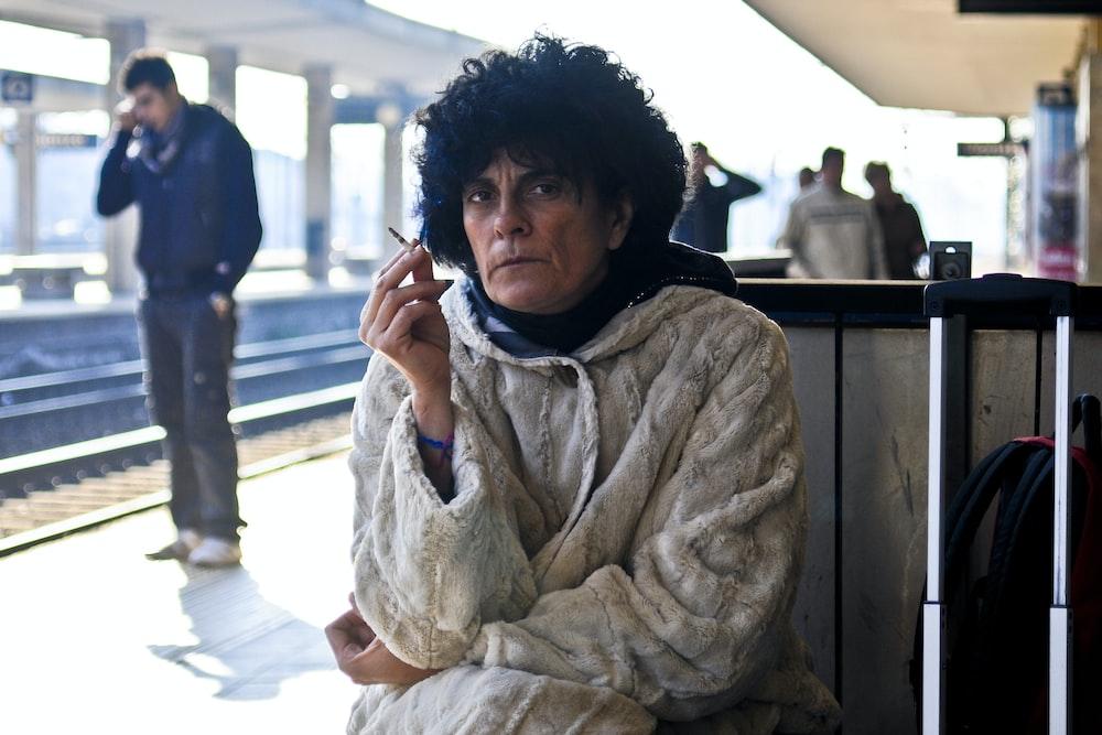 man sitting and smoking at the train station