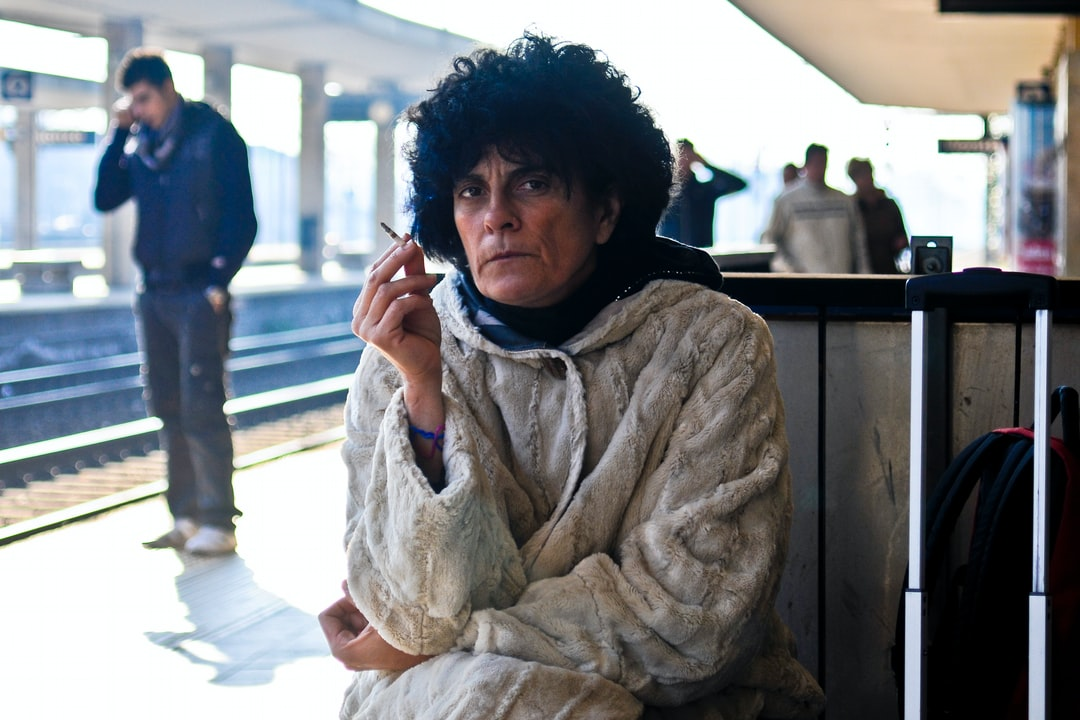 An old, moody lady smoking at a train station.