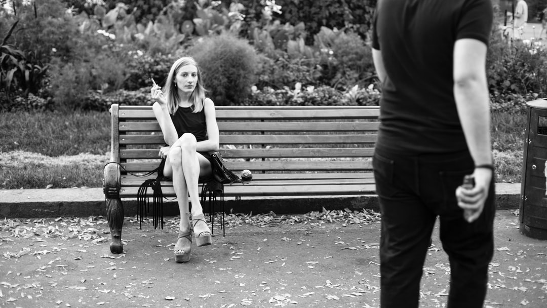 A chic cool woman sitting on a bench in a park, smoking.