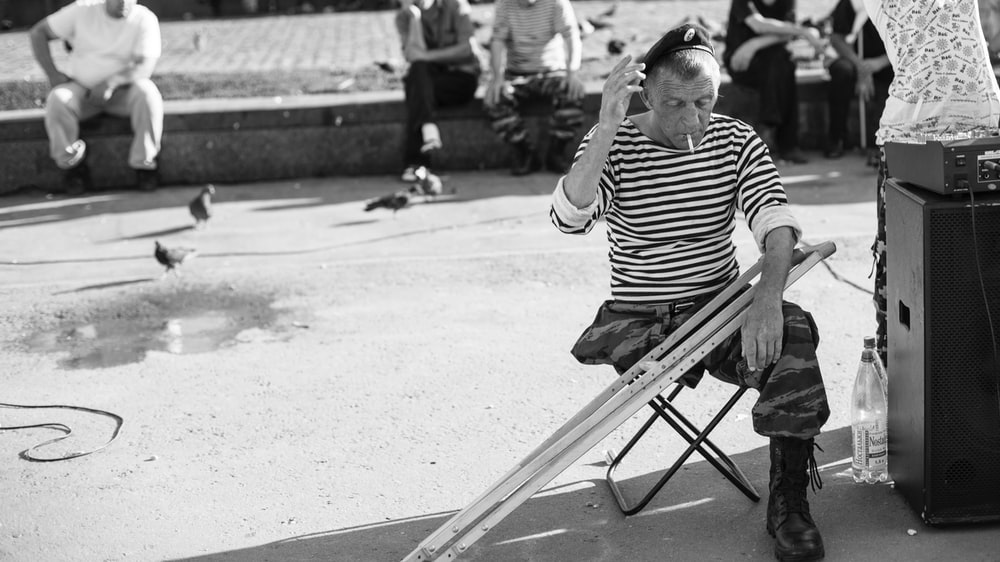grayscale photo of man sitting on folding stool with crutches in front of people