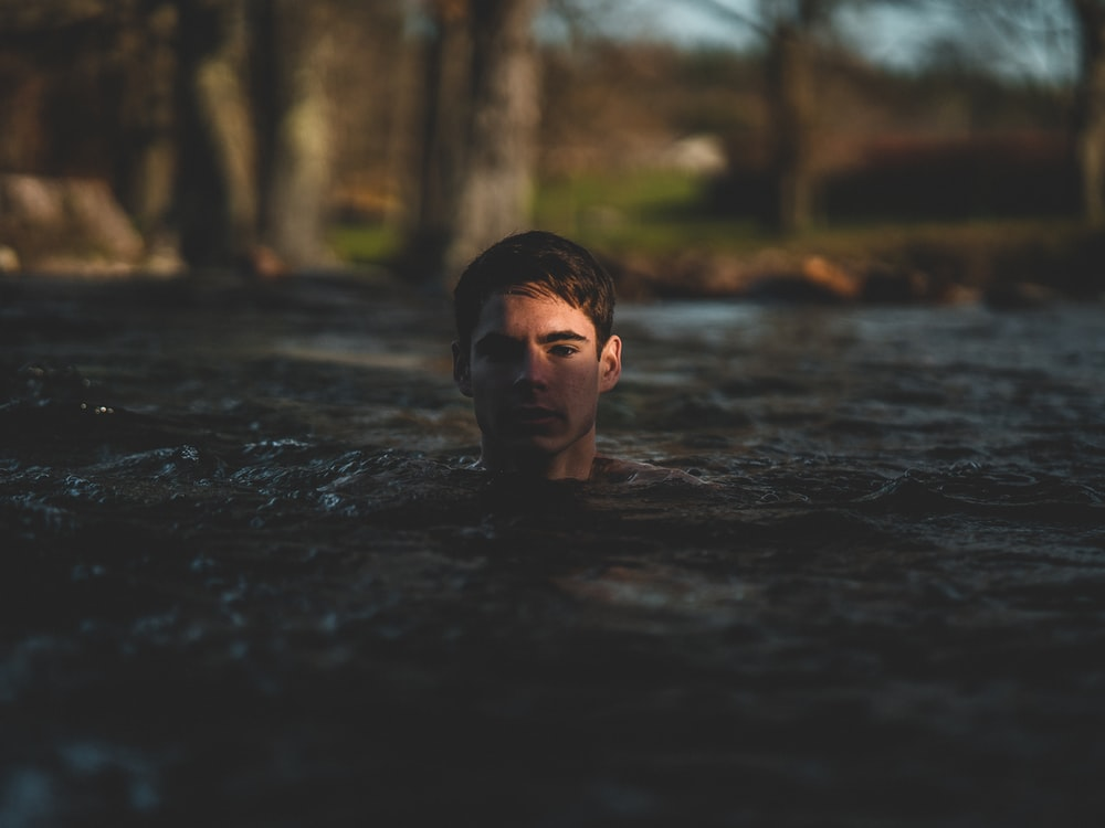 grayscale photography of man swimming