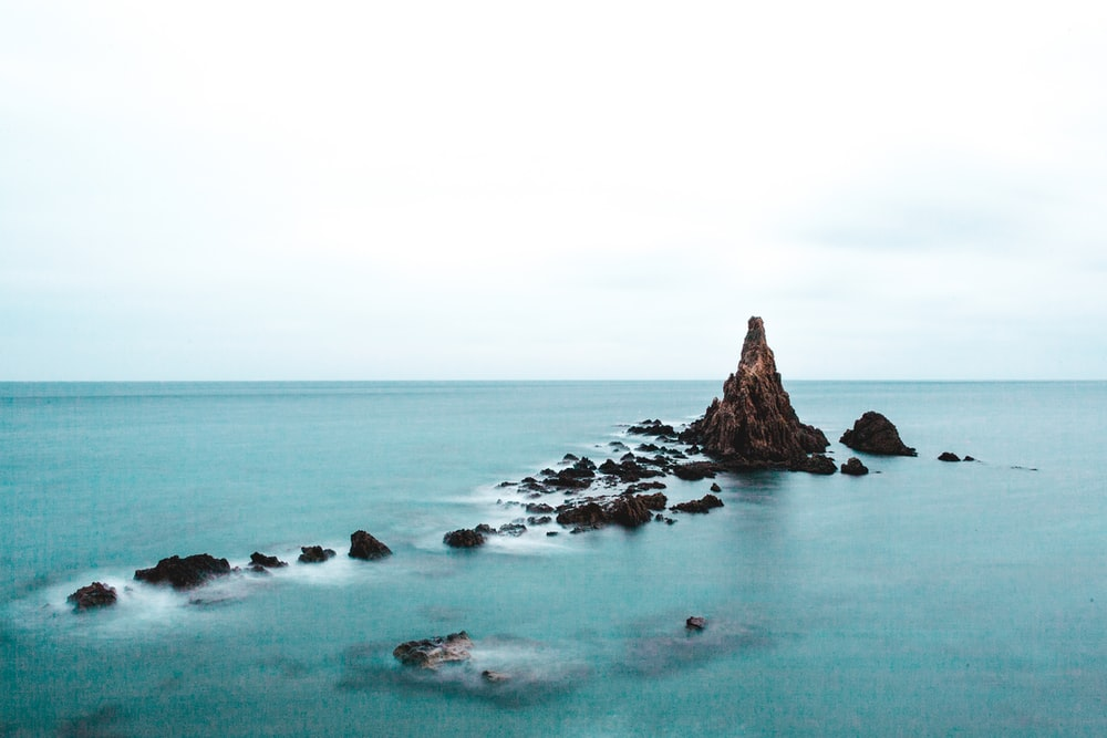 rock formation in body of water during daytime