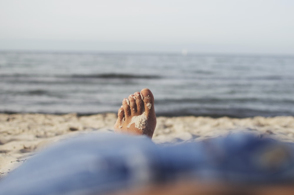 person lying on sand beside seA