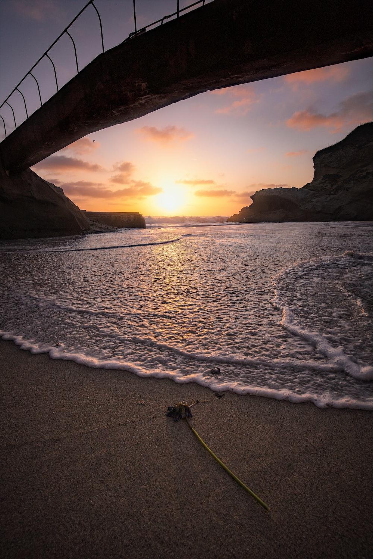 silhouette photo of bridge near sea