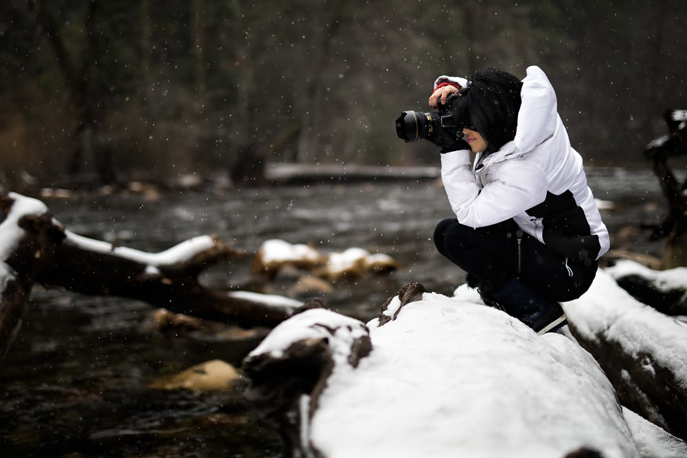 person holding camera on snow-covered surface
