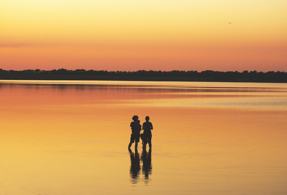 two people standing on body of water during daytime