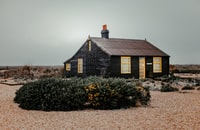 """Dungeness is a headland on the coast of Kent, England, formed largely of a shingle beach in the form of a cuspate foreland.  Perhaps the most famous house is Prospect Cottage, formerly owned by the late artist and film director Derek Jarman. The cottage is painted black, with a poem, part of John Donne's """"The Sunne Rising"""", written on one side in black lettering. But the garden is the main attraction: reflecting the bleak, windswept landscape of the peninsula, Derek Jarman's garden is made of pebbles, driftwood, scrap metal and a few hardy plants."""