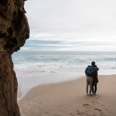 two person standing on seashore