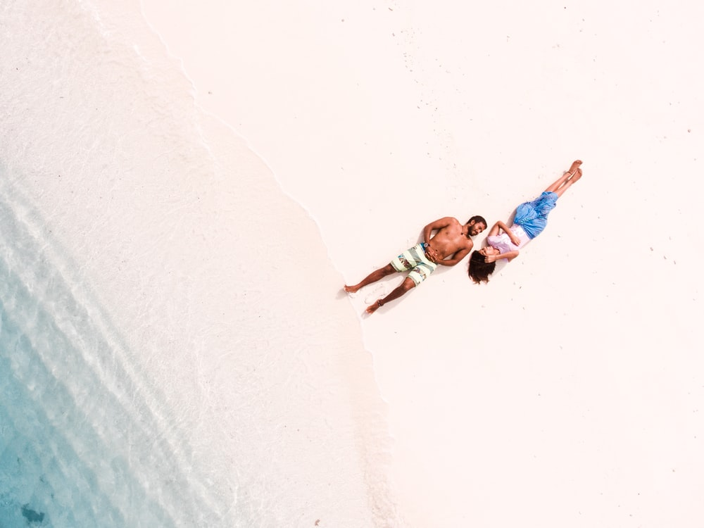 bird's eye view of man and woman lying on shore