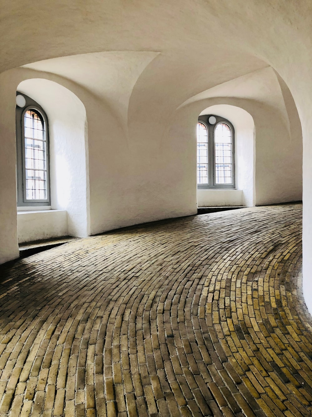 white painted swerving hall with brick floor