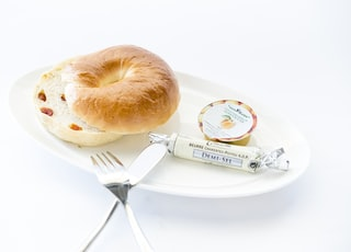 bread on white plate with fork and table knife