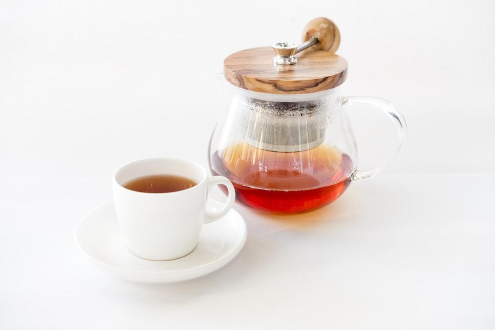 tea on glass teapot beside teacup with saucer