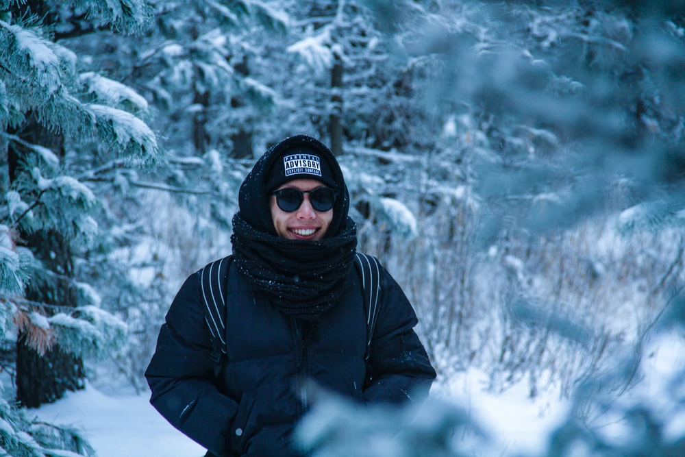 smiling man standing near snow-covered trees