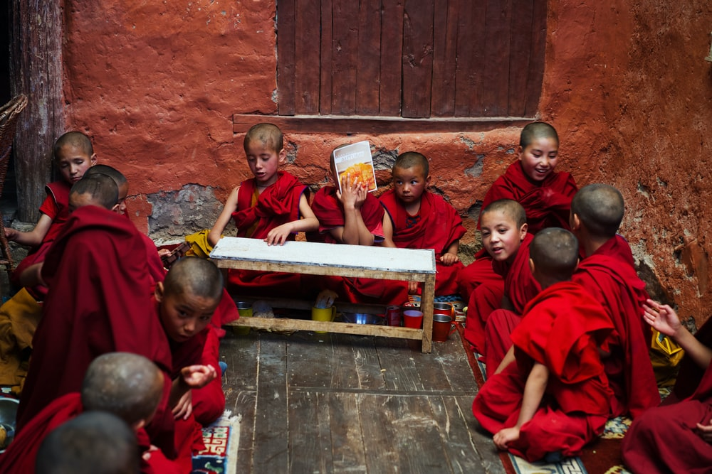 boys in red robe sitting on the floor