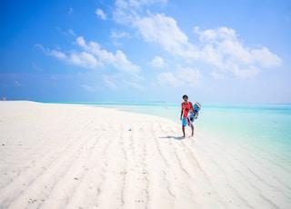 man wearing orange shirt walking on seashore