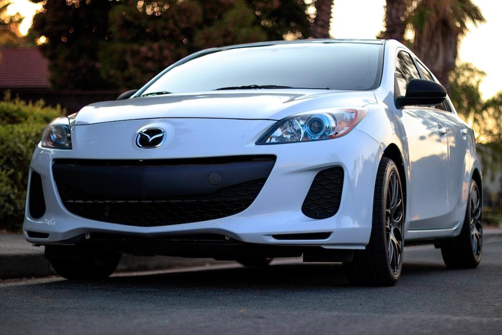 white Mazda sedan on road
