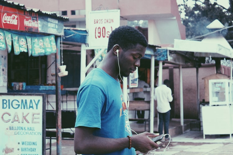 man listening to earphones near store