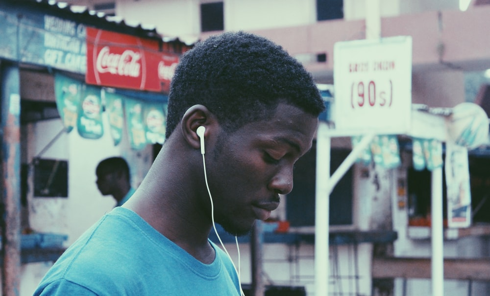 man wearing blue crew-neck shirt wearing earbuds