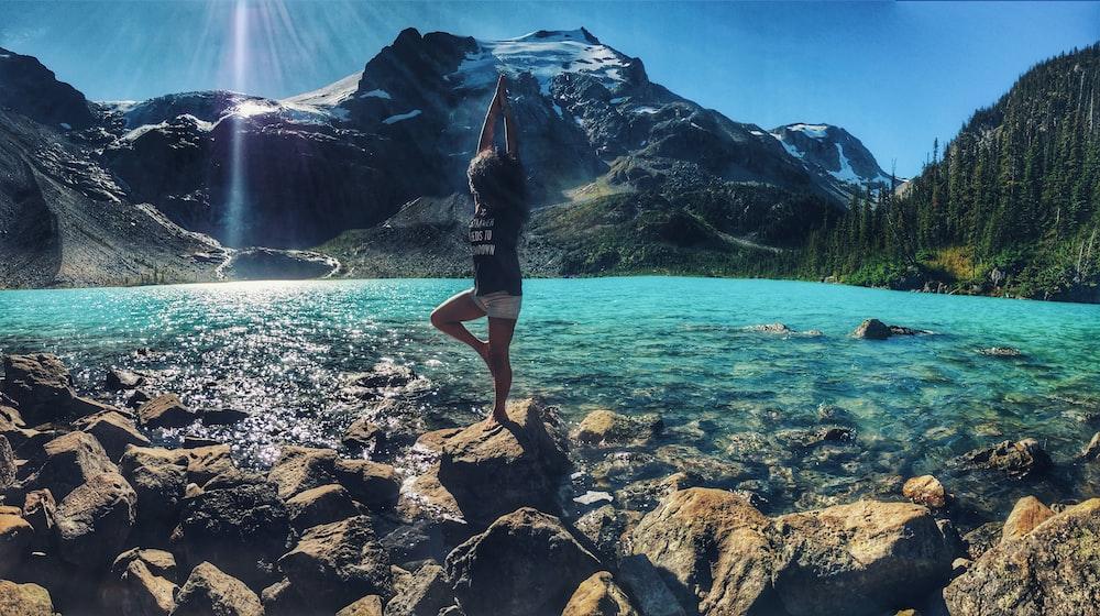 woman doing yoga pose on rock