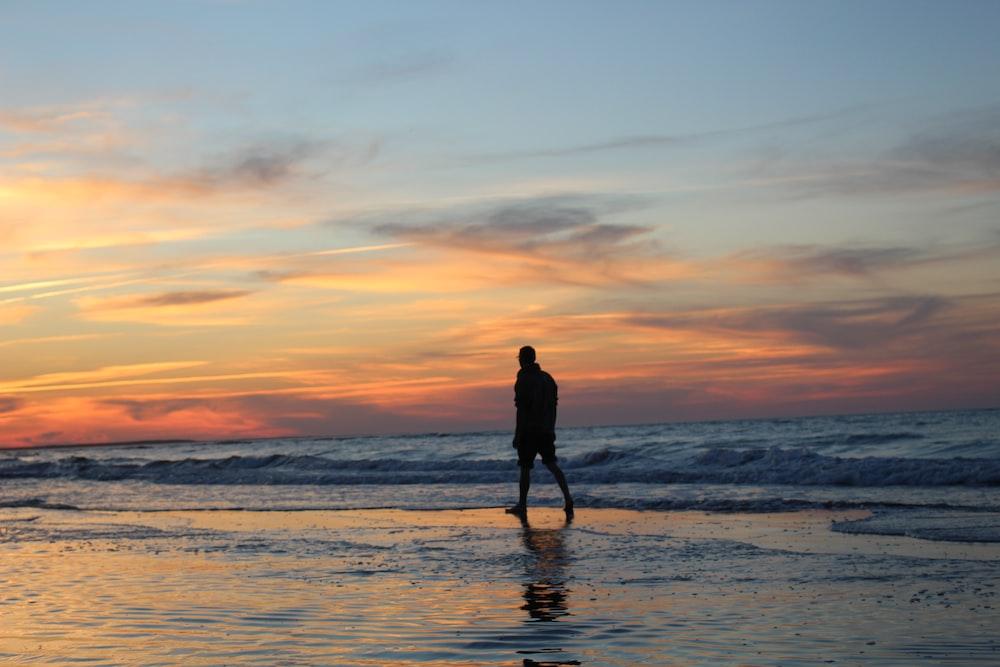 silhouette of man walking on seashore