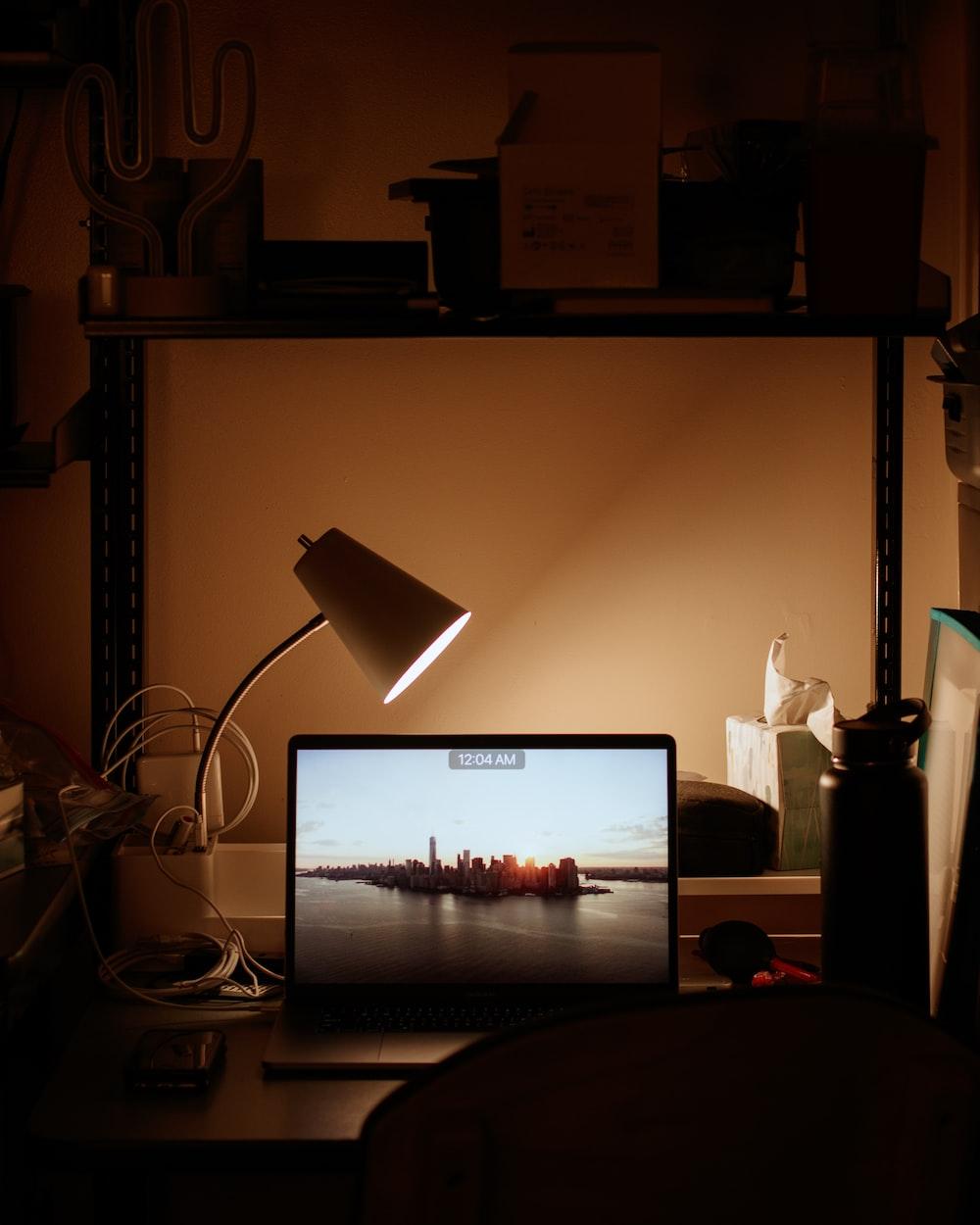 laptop turned on beside desk lamp turned on