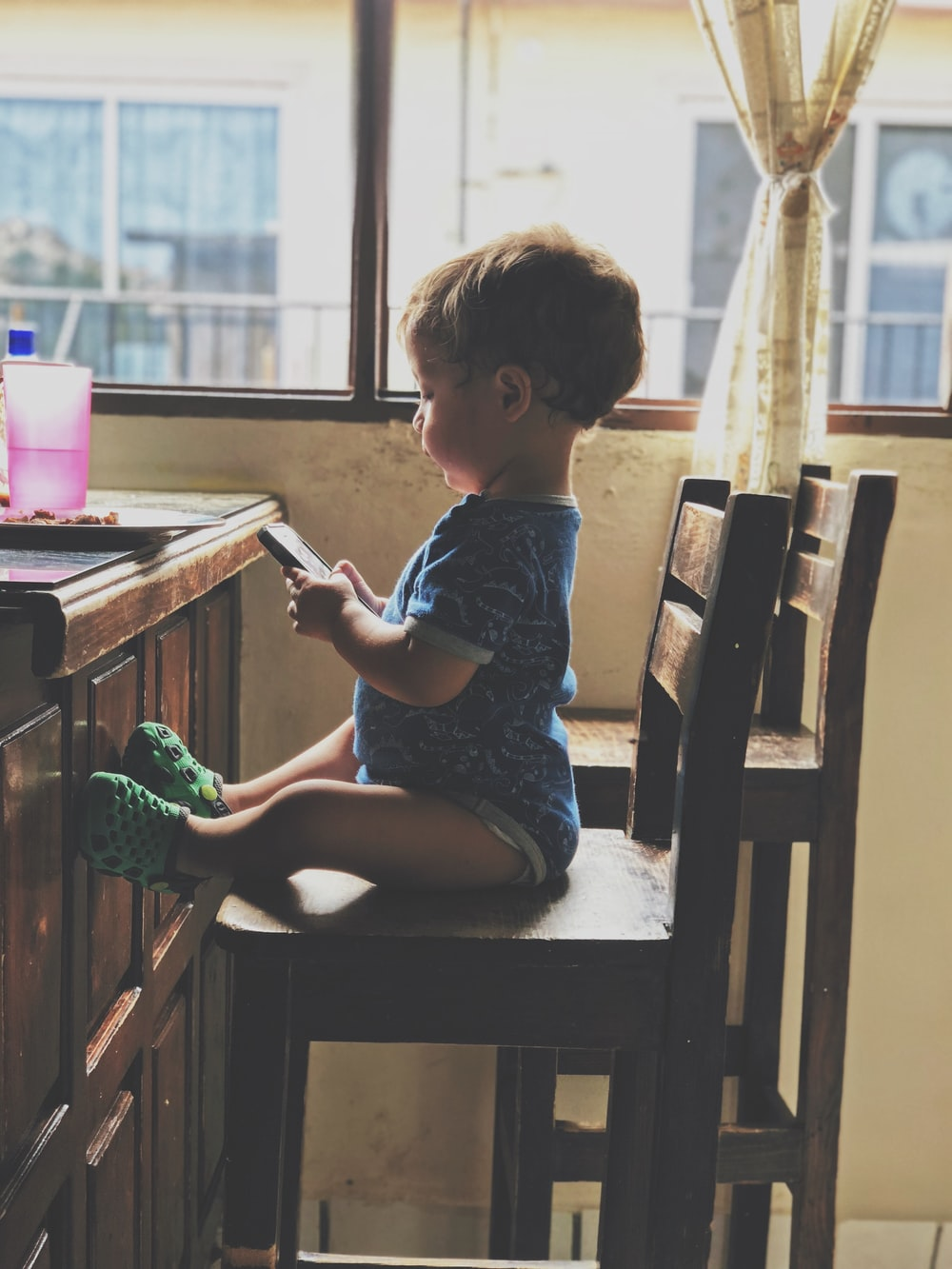 boy holding smartphone while sitting on the chair