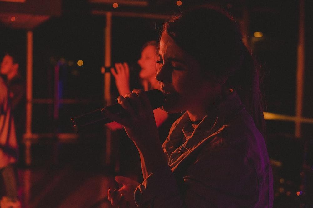 two women singing inside room