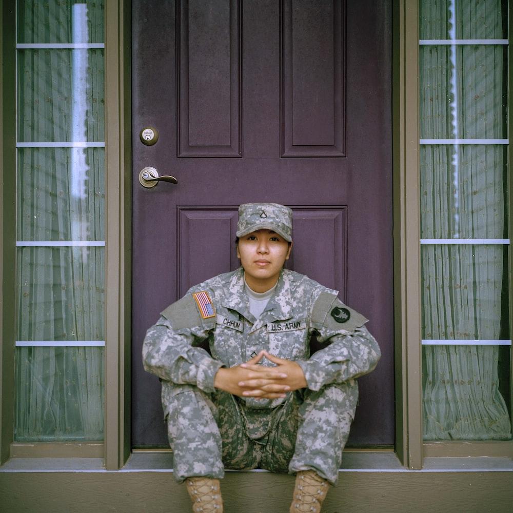woman sitting in front of closed door