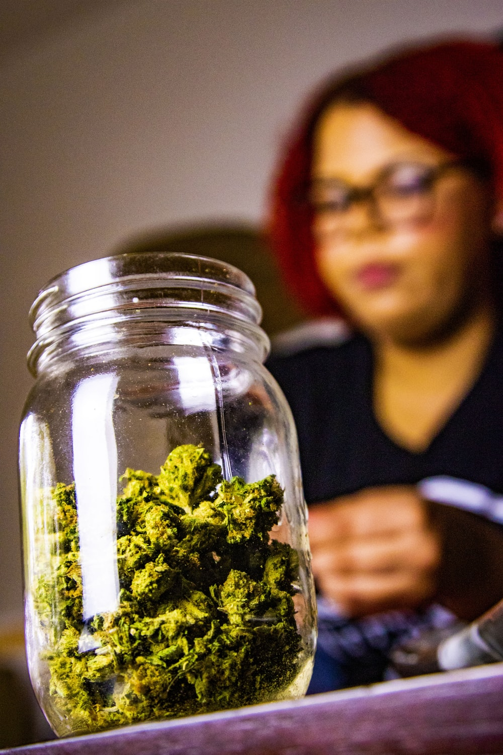selective focus photography of kush on jar near woman