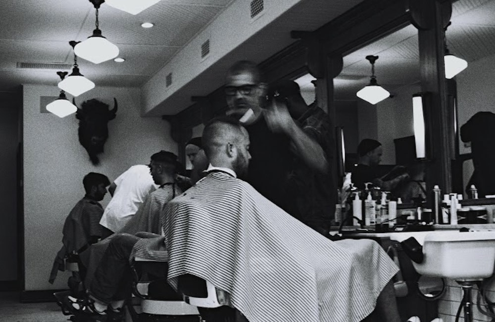 grayscale photography of man having haircur