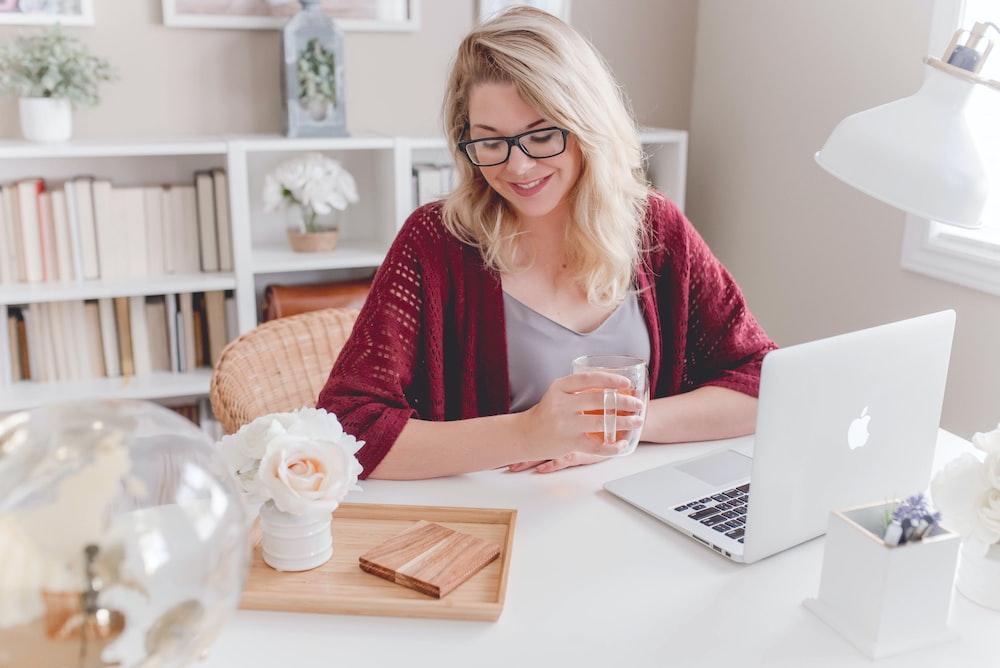 MacBookでテーブルの横に座っているガラスのマグカップを保持している笑顔の女性