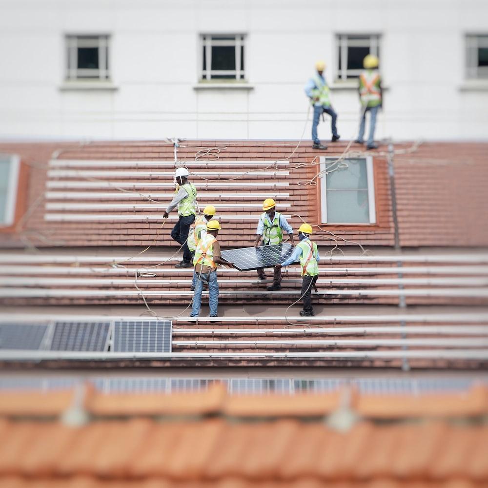 man holding solar panel on roof