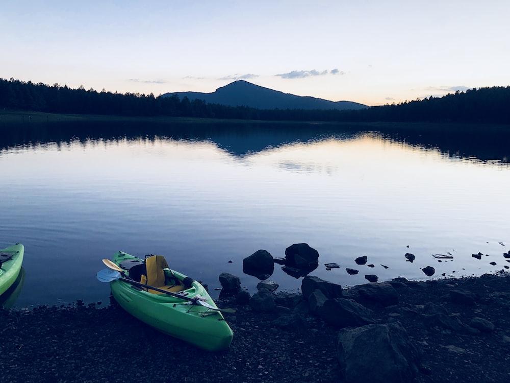 empty green kayak on lake