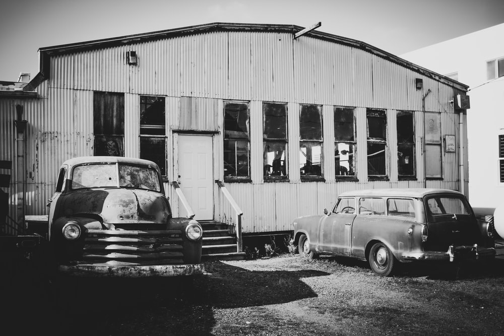 grayscale photo of cars parked in front of building