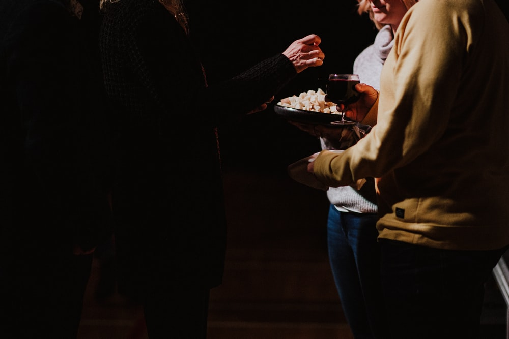 three person standing and holding glass of wine and food