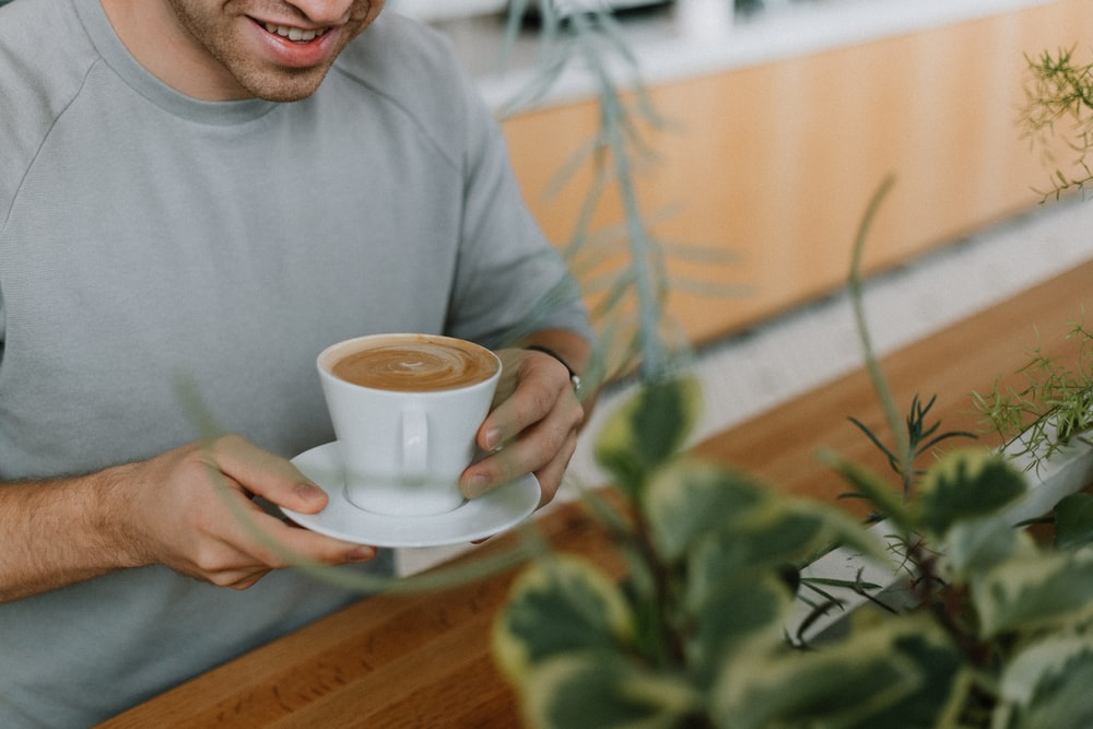 shallow focus photo of person holding white ceramic mug and saucer