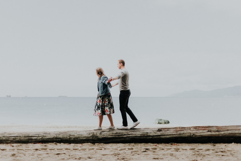 woman and man walking by the beach