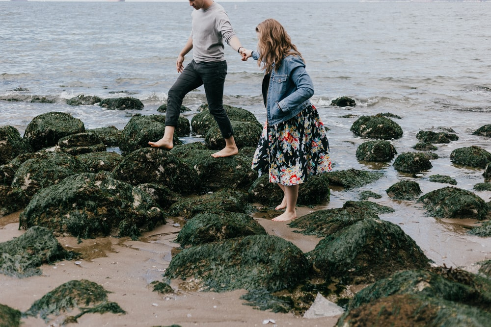 man and woman holding hand together while stepping on rocks near sea